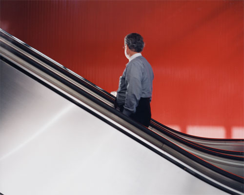 A photography of a man on an elevator with his back turned to illustrate a quote from Tiqqun's Theory of Bloom