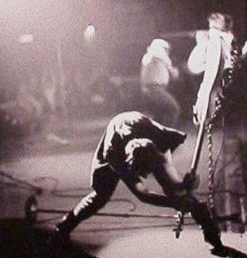Photo of  bassist Paul Simonon smashing his guitar on stage, September 20, 1979
