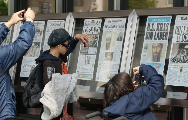 Passers-by take pictures of newspaper headlines reporting the death of Osama Bin Laden, in front of the Newseum, on May 2, 2011 in Washington, DC. (Mark Wilson/Getty Images)