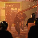 A rioter throws a burning wooden plank at police in Tottenham Aug. 7, 2011. (Lewis Whyld/PA/AP)