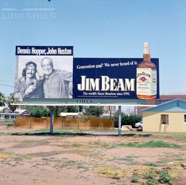 Bill board advertisement for Jim Beam whisky featuring Dennis Hopper and John Huston, 1972