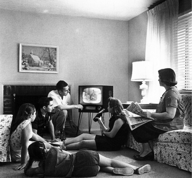 A family gathered in front of a television set, photo by Evert F. Baumgardner, ca. 1958