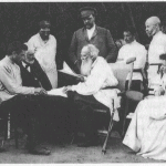"Original captions from William Nickell's book The Death of Tolstoy (2010, p. 23): ""Tolstoy reads a draft of his article ""On Madness"" to a circle of Tolstoyans. From left to right are F. A. Strakhov, Valentin Bulgakov, the physician A. S. Buturlin, the skopets A. Ya. Grigor'ev, Chertkov, M. P. Balakin, Dushan Makovitskii, Anna Chertkova, L. P. Sergeenko and the actor P. N. Orlenev."