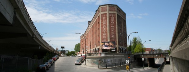 """A photo from Tim Hetherington series """"Sleeping Soldiers"""" is displayed on a billboard mounted on an old warehouse photographed many years before by Canadian photographer Gabor Szilasi."""
