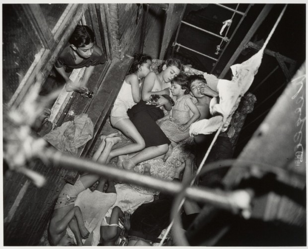 """Children on Fire Escape"" by Weegee (Arthur Fellig), gelatin silver print, 32.2 x 40.3 cm. (12 11/16 x 15 7/8 in.), 1938. © Weegee / International Center of Photography."