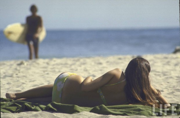 Woman lying on the beach by Co Rentmeester, California, April 1970