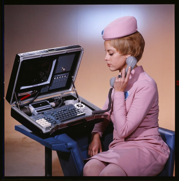In this production photo from 2001: A Space Odyssey, a space stewardess is seen elegantly using a portable videophone. If the blue, circle badge on her uniform is any indication she's stationed, in the film, at Clavius Base which served as a Research Center when the first monolith was discovered on the Moon.