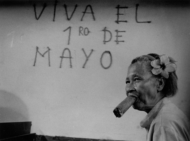 "A photo by Ernesto Bazan shows a cigar factory worker while she begins her shift by rolling a cigar (1997). Behind her, on the wall, are inscribed the words ""Viva el 1ro de Mayo"""