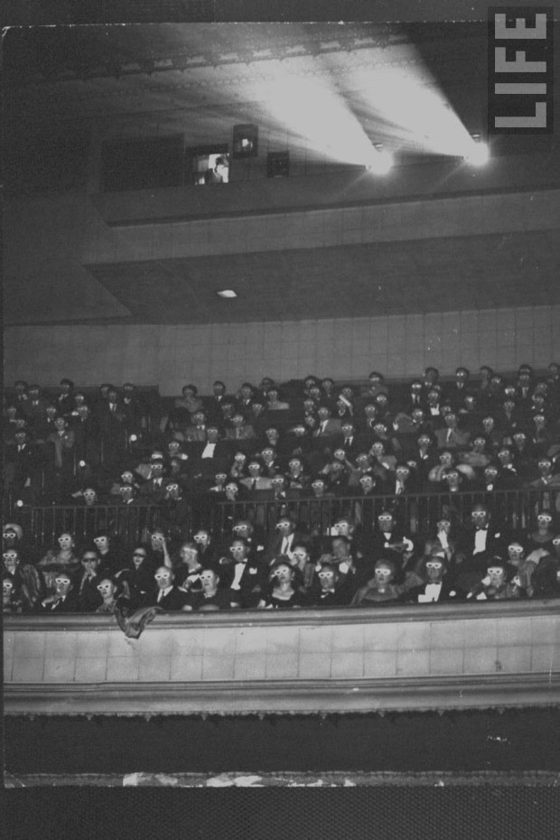 """Caption from LIFE: Formally attired audience sporting 3-D (3D) glasses during opening night screening of film """"Bwana Devil,"""" the 1st full length color 3-D (aka """"Natural Vision"""") motion picture, seated in balcony under projection rm., at Paramount Theater. Photo by J.R. Eyerman, 1952"""