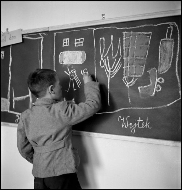 """POLAND. Warsaw. 1948. In a school for mentally disturbed children, one of them, Wojtek, draws his home on a blackboard"" by David Seymour. Magnum Image Reference SED1948029W00010/5-110 (NYC122328). © The Estate of David Seymour."