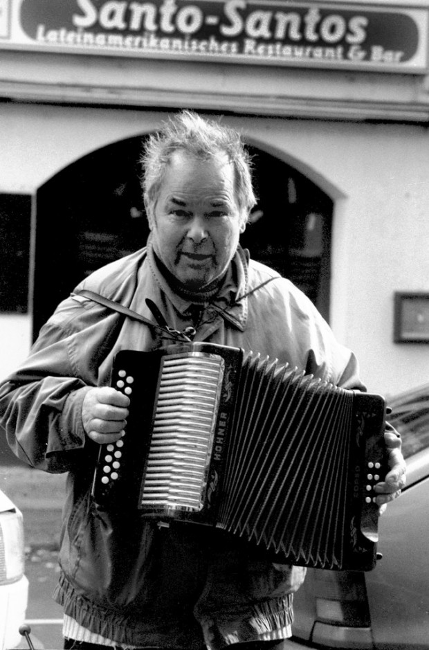A black-and-white portrait depicting Bruno Schleinstein while he plays the accordion in the streets of Berlin. Ekkehard Wölk, 2004.