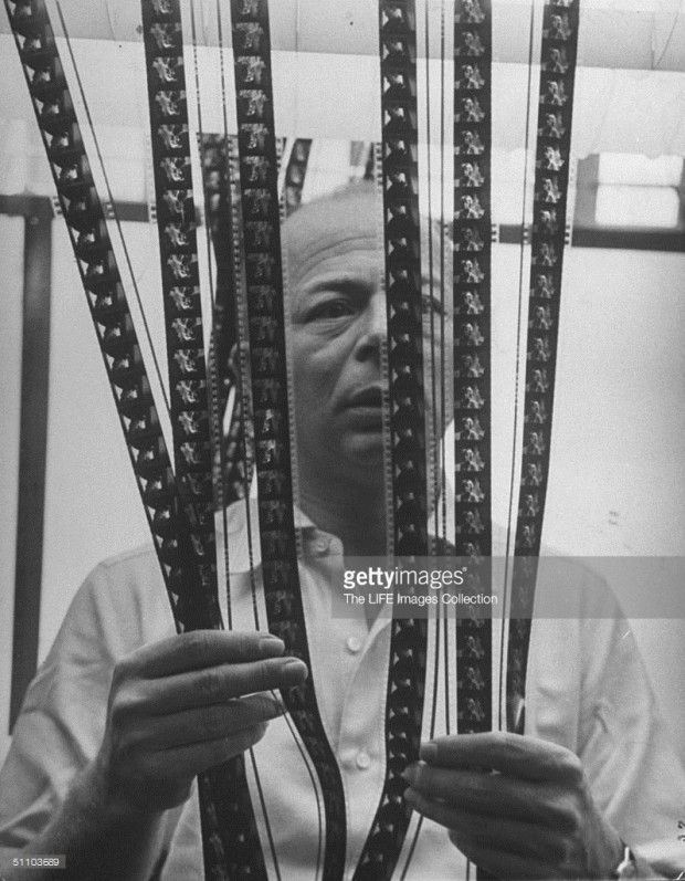 """Movie director Billy Wilder standing behind strips of film in cutting room while he decides which should go into finished movie."" Photo by Bob Landry. Image retrieved from Getty Images."