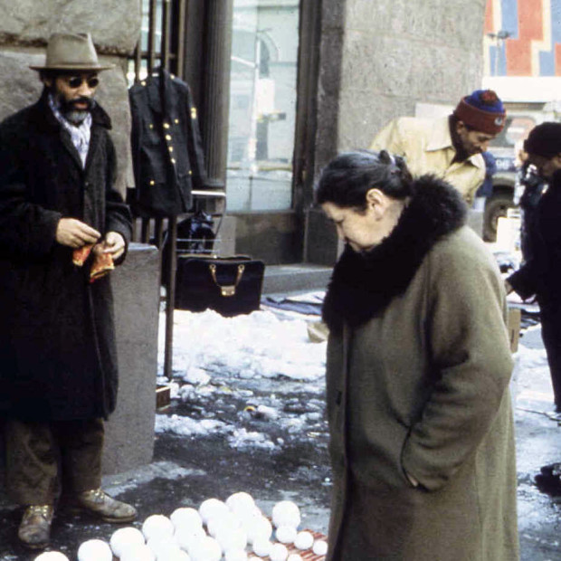 Lady looking at David Hammons selling snow balls in New York, 1983. Photo by Dawood Bey. Image retrieved from Shadow Vue.